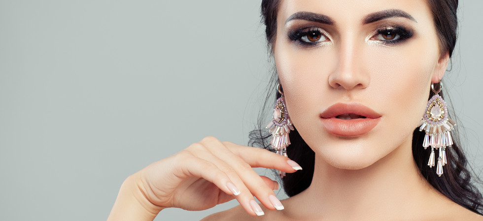 Jewellery women. Brunette woman with makeup and pink earrings closeup portrait